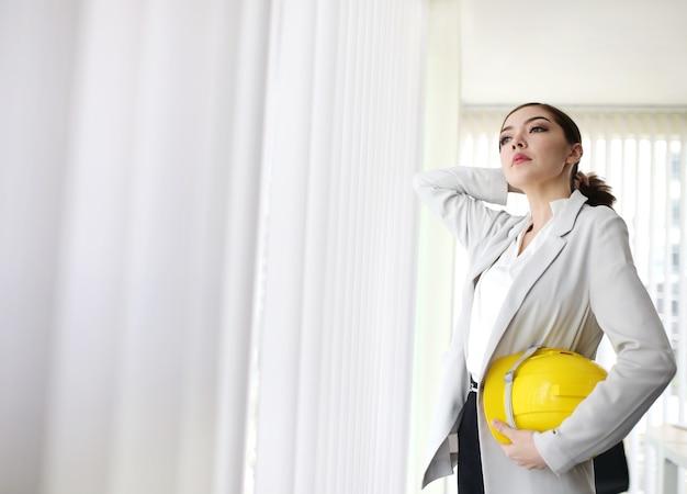 Donna di affari astuta con il casco dell'ingegnere della tenuta della mano del vestito che sta nell'ufficio di affari