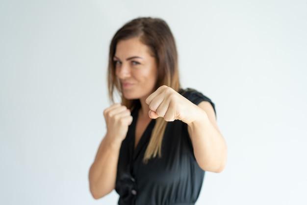 Donna di affari atletica positiva che perfora alla macchina fotografica.