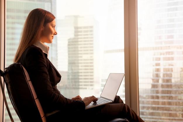 Donna di affari attraente che gode del tramonto, rilassantesi nel cha dell'ufficio