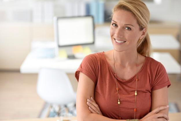 Donna di affari attraente che si leva in piedi nell'ufficio