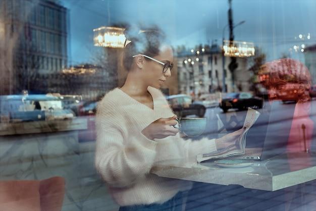 Donna di affari attraente nella conversazione obile degli occhiali ottici con l'amico tramite il dispositivo dello smartphone giovane donna positiva che parla sul telefono che si siede al computer portatile in caffetteria