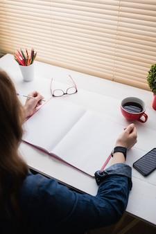 Donna di affari casuale che lavora al suo scrittorio in ufficio