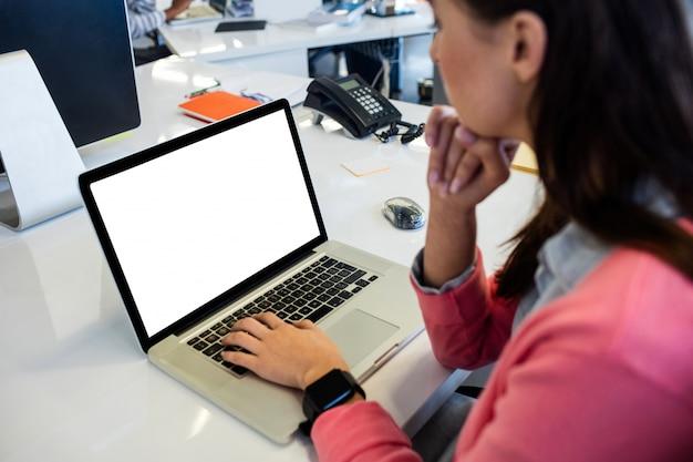 Donna di affari casuale che per mezzo di un computer portatile