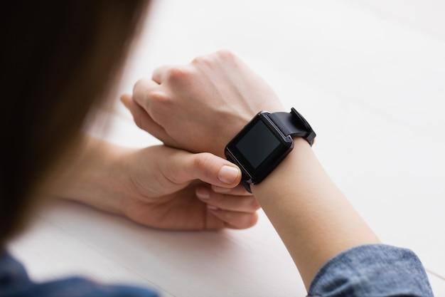 Donna di affari casuale che utilizza il suo orologio astuto al suo scrittorio in ufficio