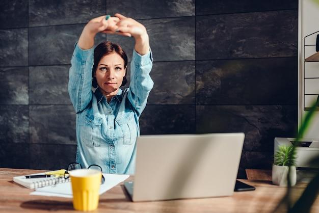 Donna di affari che allunga le braccia nell'ufficio
