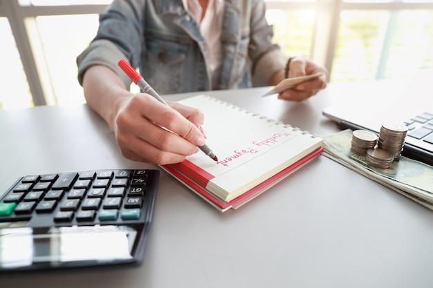 Donna di affari che annota la lista mensile di pagamento sul taccuino con il computer e la carta di credito