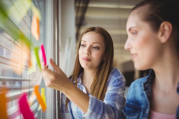 Donna di affari che attacca le note adesive sulla finestra in ufficio
