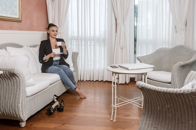Donna di affari che beve bevanda calda nella camera di albergo