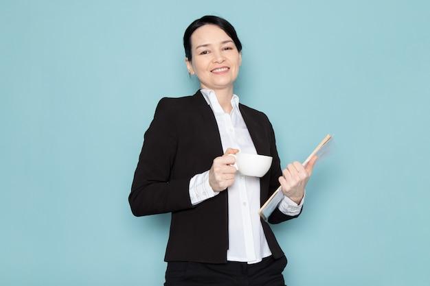 Donna di affari che beve caffè e che tiene rivista