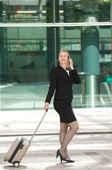 Donna di affari che cammina e che chiama con il telefono cellulare all'aperto