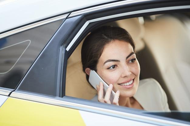 Donna di affari che chiama dal taxi