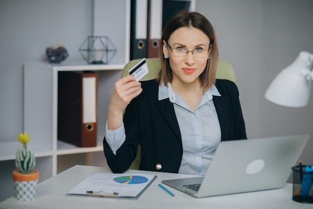 Donna di affari che compera online con il computer portatile in ufficio. carta di credito della banca della tenuta della giovane donna a disposizione e che compra dal computer
