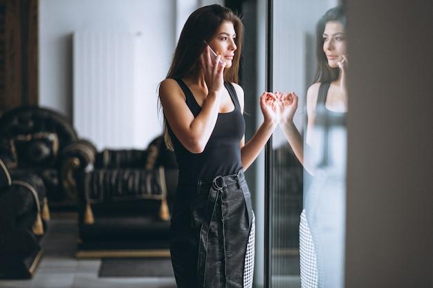 Donna di affari che comunica sul telefono che fa una pausa la finestra
