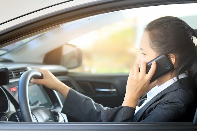 Donna di affari che conduce automobile e che parla un telefono