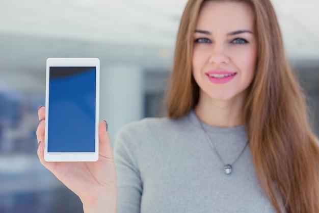 Donna di affari che dimostra l'esposizione dello smartphone alla macchina fotografica