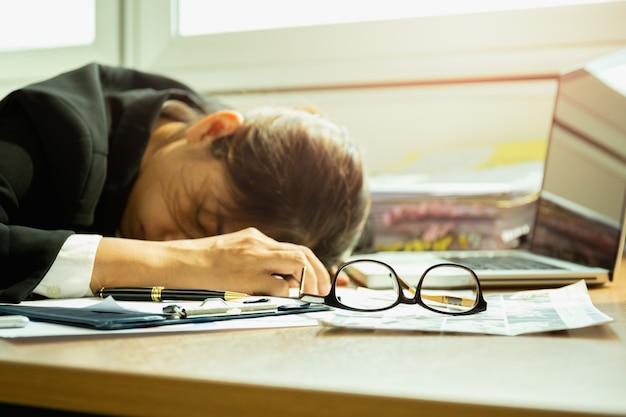 Donna di affari che dorme al fuoco selezionato scrittorio del lavoro sui vetri.
