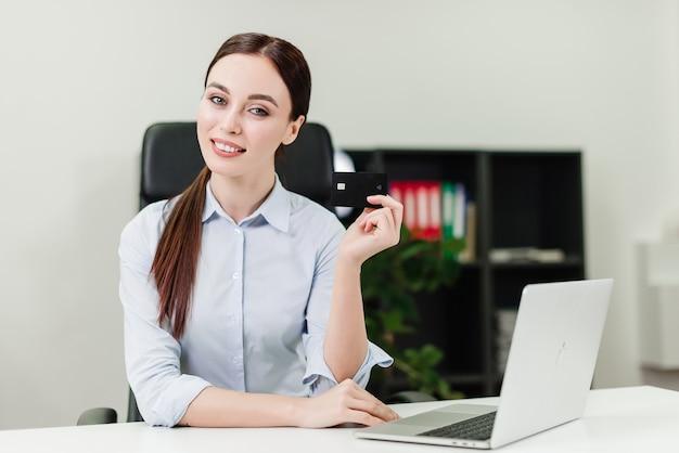 Donna di affari che effettua i pagamenti online e che collega i soldi facendo uso della carta di credito e del computer portatile nell'ufficio