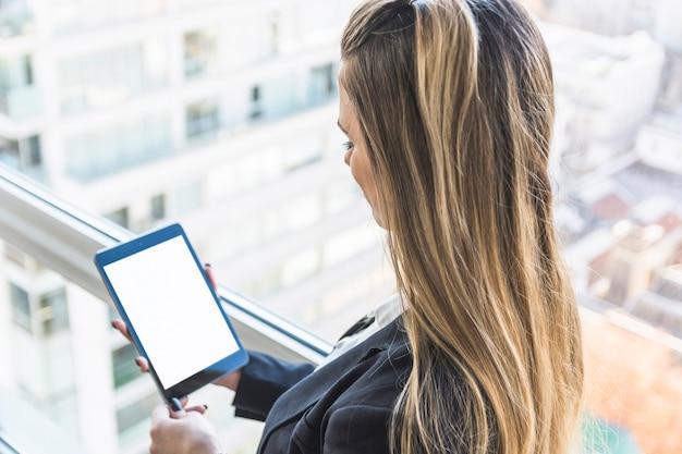 Donna di affari che esamina compressa digitale con lo schermo di visualizzazione bianco