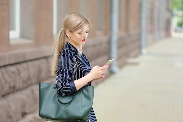 Donna di affari che esamina telefono cellulare sulla via.