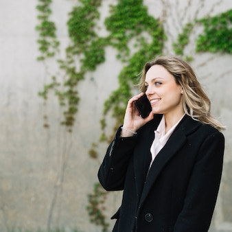Donna di affari che fa chiamata di telefono all'aperto