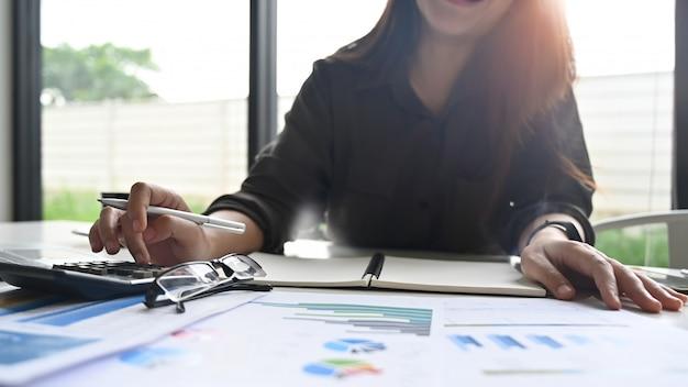 Donna di affari che fa finanziaria e calcolatrice