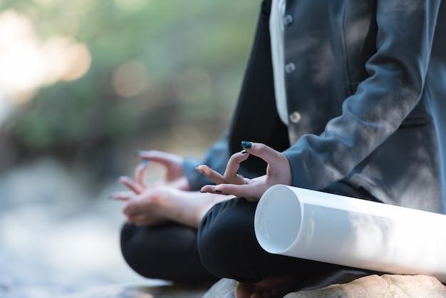 Donna di affari che fa meditazione di yoga per rilassarsi nel parco.
