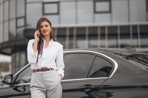 Donna di affari che fa una pausa l'automobile e che per mezzo del telefono