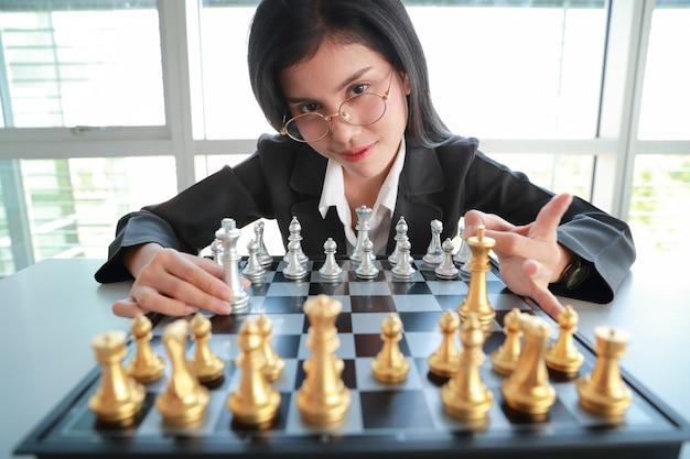 Donna di affari che gioca l'idea del gioco della scacchiera di strategia e direzione della gestione