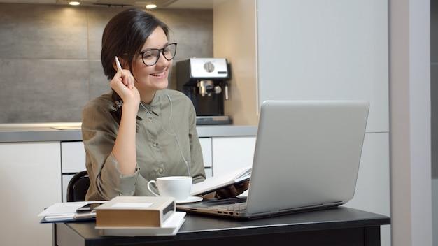 Donna di affari che ha una video chat facendo uso delle cuffie e del computer portatile a casa. formazione online o lavoro a distanza