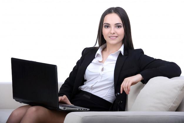 Donna di affari che lavora ad un computer portatile che si siede sul sofà.