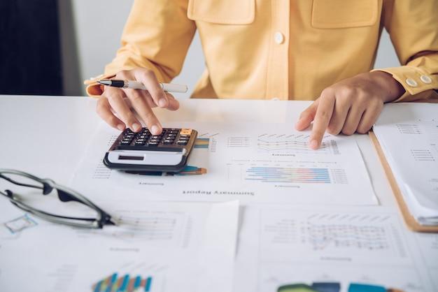 Donna di affari che lavora ai conti nell'analisi di affari con i grafici e la documentazione.