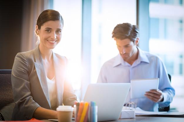 Donna di affari che lavora al computer portatile con il collega