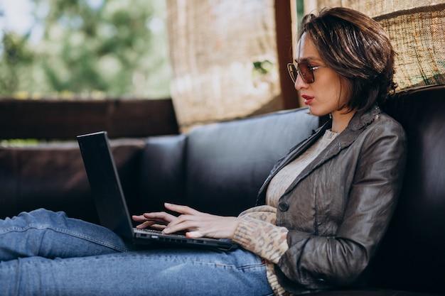 Donna di affari che lavora al computer portatile fuori casa