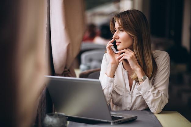 Donna di affari che lavora al computer portatile in un caffè