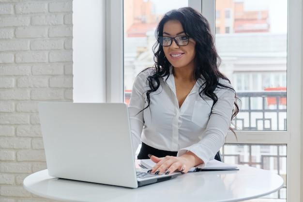 Donna di affari che lavora al suo computer portatile