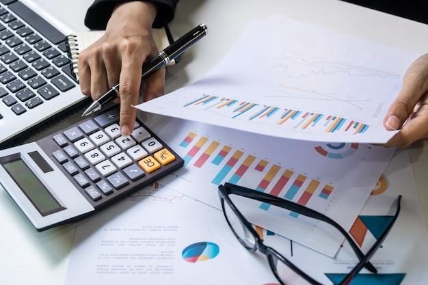 Donna di affari che lavora all'ufficio dello scrittorio con analisi delle statistiche del grafico di vendita