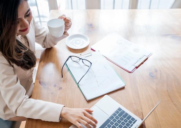 Donna di affari che lavora alla sua scrivania con documento documento e laptop