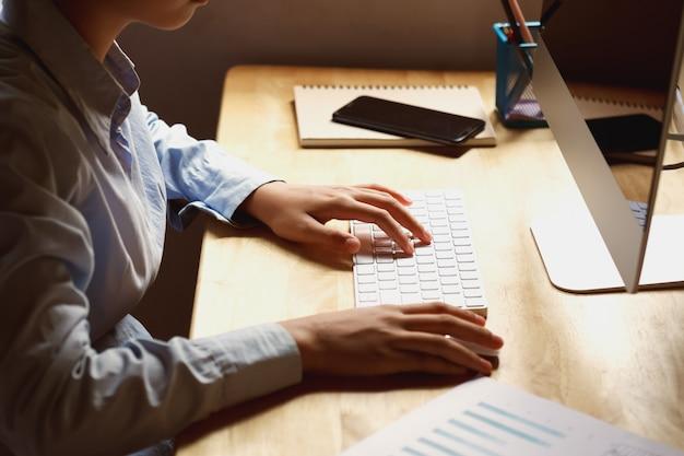 Donna di affari che lavora allo scrittorio facendo uso del computer portatile per i dati del controllo di finanza in ufficio