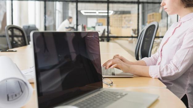 Donna di affari che lavora con il computer portatile in ufficio