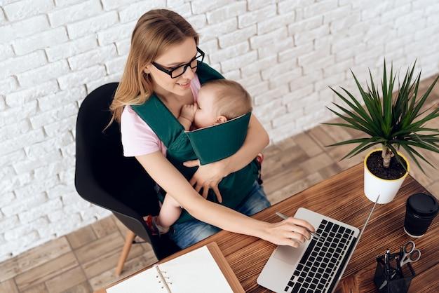 Donna di affari che lavora con il neonato nell'imbracatura del bambino