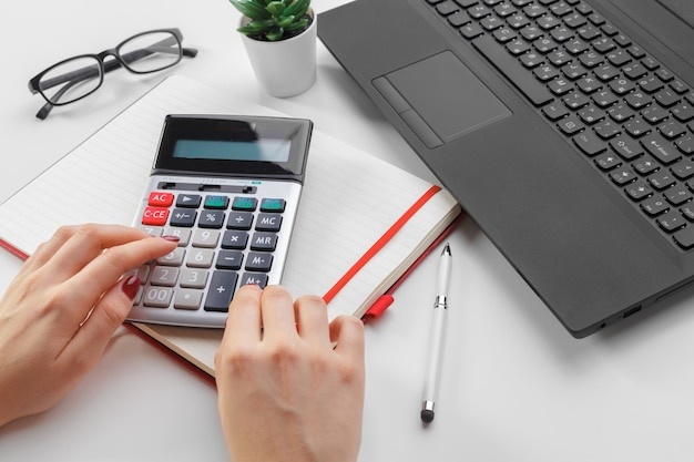 Donna di affari che lavora con la mano di dati finanziari facendo uso del calcolatore
