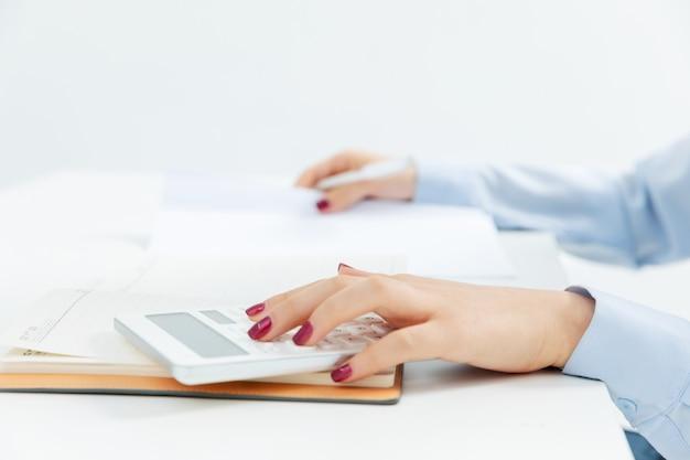Donna di affari che lavora con un calcolatore con una priorità bassa bianca