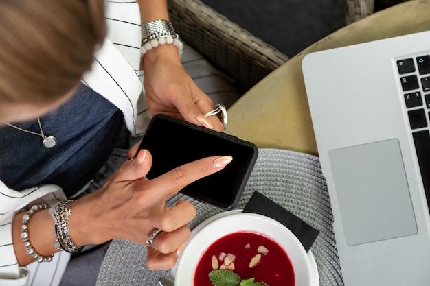 Donna di affari che lavora durante il pranzo con insalata che si siede al ristorante vegano sui bei precedenti verdi della parete