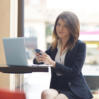 Donna di affari che lavora fuori dell'edificio per uffici con i dispositivi digitali