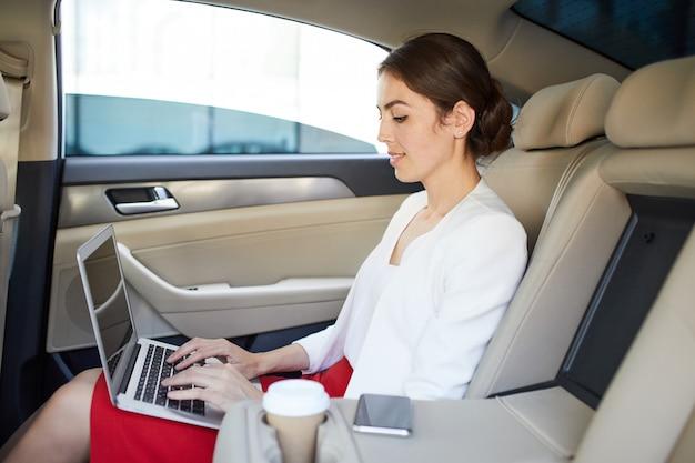 Donna di affari che lavora in auto