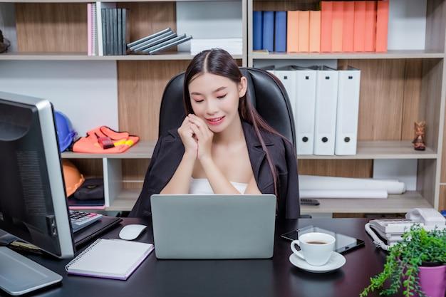 Donna di affari che lavora nell'ufficio con un sorriso mentre sedendosi.