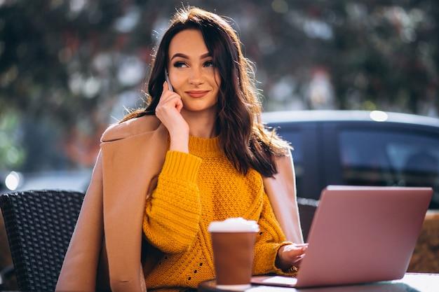 Donna di affari che lavora su un computer e che beve caffè