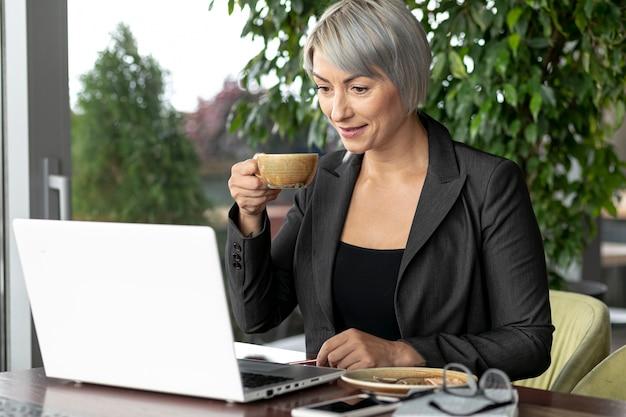 Donna di affari che mangia caffè mentre lavorando