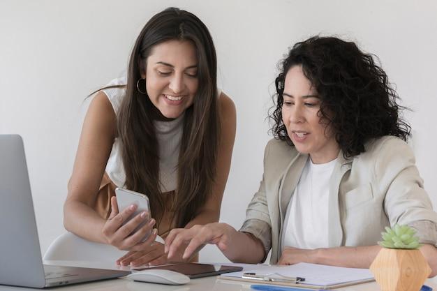 Donna di affari che mostra al suo collega qualcosa sul telefono