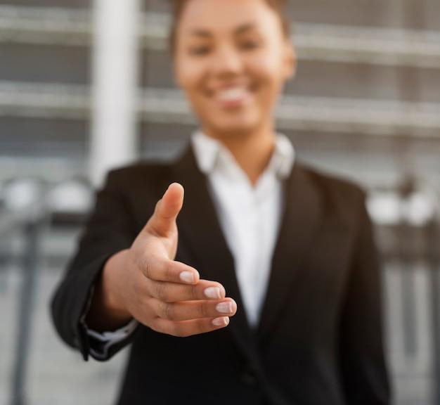 Donna di affari che mostra alto vicino della mano